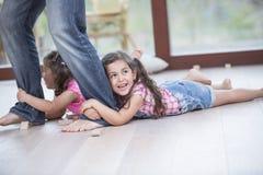 Sección baja de las muchachas de fricción del padre en suelo de parqué Foto de archivo libre de regalías