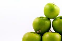 Seccione el tiro de un grupo de manzanas verdes en un fondo blanco Fotos de archivo