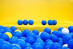 Sechs blaue Bälle auf der gelben Bank Lizenzfreie Stockfotografie