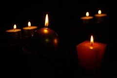 Sechs brennende Kerzen auf einem schwarzen Hintergrund Lizenzfreies Stockbild