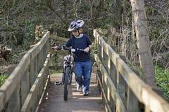 Sechs Einjahresjunge, der ein Fahrrad drückt Lizenzfreie Stockfotografie