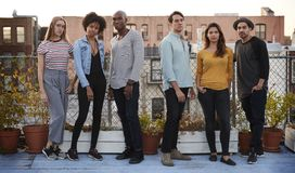 Sechs erwachsene Freunde, die zusammen auf der Dachspitze, in voller Länge stehen stockfotos