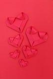 sechs faltende rote Papierherzen auf Rot für Valentinsgrußmuster und -ba Lizenzfreies Stockfoto