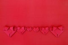 sechs faltende rote Papierherzen auf Rot für Valentinsgrußmuster und -ba Lizenzfreie Stockbilder