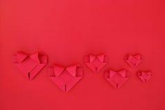 sechs faltende rote Papierherzen auf Rot für Valentinsgrußmuster und -ba Lizenzfreie Stockfotos