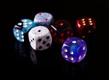 Sechs Farbe würfelt auf schwarzem Brett Lizenzfreie Stockfotos