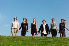 Sechs Freunde gehen auf die Wiese, die Händen angeschlossen wird Stockfotografie