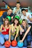 Sechs Freunde mit Kugeln für Bowlingspiel stellen o.k. dar Lizenzfreie Stockfotos