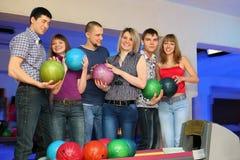 Sechs Freunde stehen und halten Kugeln für Bowlingspiel an Stockfoto