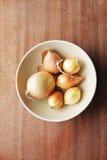 Sechs gelbe Zwiebelköpfe in ein tiefen keramischen Platte bezhegogo Farben auf einem hölzernen Brett Stockbilder