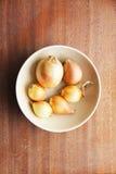 Sechs gelbe Zwiebelköpfe in ein tiefen keramischen Platte bezhegogo Farben auf einem hölzernen Brett Stockbild