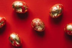 Sechs goldenes gef?rbt und verziert mit Scheine Ostereiern auf rotem Hintergrund lizenzfreies stockbild