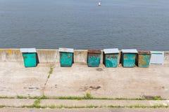 Sechs (6) grüne Abfallbehälter, die auf den Stein-embankmen stehen Lizenzfreie Stockfotos