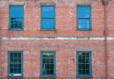 Sechs grünes Windows auf altem Backsteinbau Stockfotografie