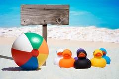 Sechs Gummienten und Holzschild auf dem Strand Lizenzfreie Stockbilder