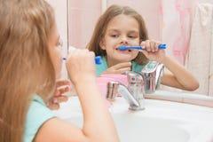 Sechs jähriges Mädchen, das den Spaß putzt seine Zähne hat, schauen im Spiegel im Badezimmer lizenzfreies stockfoto