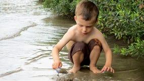 Sechs Jährigjunge, der im Sand auf dem See spielt Lizenzfreie Stockfotos