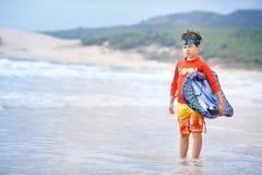 Sechs Jahre alte Junge mit Brandungsbrett auf exotischem Strand Stockfoto