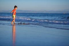 Sechs Jahre alte Junge mit Brandungsbrett auf exotischem Strand Lizenzfreie Stockfotografie