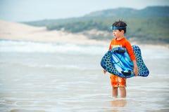 Sechs Jahre alte Junge mit Brandungsbrett auf exotischem Strand Lizenzfreies Stockfoto