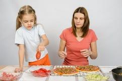 Sechs Jährigmädchen nimmt Platte von Ausschnitttomaten für Pizza unter Aufsicht der Mama Stockbilder
