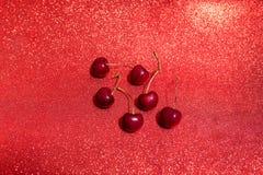 Sechs Kirsche auf Funkelnhintergrund Stockfotografie
