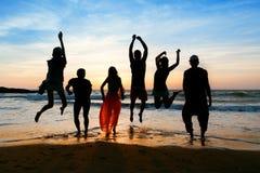 Sechs Leute, die auf Strand bei Sonnenuntergang springen Stockfotografie