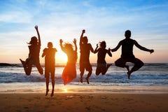 Sechs Leute, die auf Strand bei Sonnenuntergang springen Stockfotos