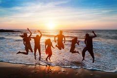 Sechs Leute, die auf Strand bei Sonnenuntergang springen Lizenzfreie Stockfotografie