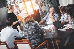 Sechs Leute, die im Dachbodenraum arbeiten Startsitzung Coworking Tee Stockfotos