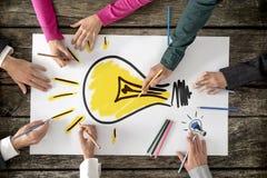 Sechs Leute, Männer und Frauen, zeichnende helle gelbe Glühlampe Lizenzfreies Stockfoto