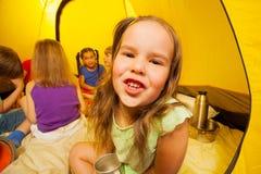 Sechs lustige Kinder sitzen in einem Zelt Stockbild