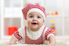 Sechs Monate alte Baby, die auf Teppich auf Boden in der Kindertagesstätte liegen Lizenzfreie Stockfotografie