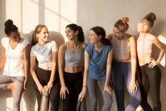 Sechs multiethnische Mädchen, die Gespräch nach Training genießen stockfoto