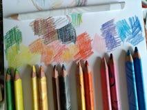 Sechs Paare der farbigen Bleistifte liegen nahe bei dem Abstand und malen auf Papier mit farbigen Stellen, kreative Umwelt, fein lizenzfreies stockbild