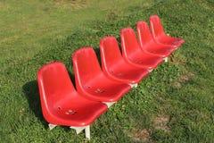 Sechs rote Plastiksätze mit Blau sitzen in Folge auf grünem Gras Sitze für Zuschauer oder Teams auf einem ländlichen Fußballplatz lizenzfreie stockbilder