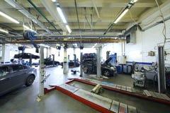Sechs schwarze Autos stehen in der Garage mit spezieller Ausrüstung Stockbilder