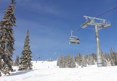 Sechs Snowboarder reiten den Stuhlaufzug in einem Wald Lizenzfreies Stockfoto