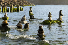 Sechs Steinhaufenstand gegen die ankommenden Gezeiten Stockfotografie