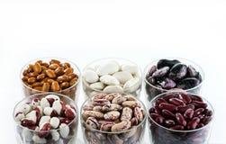 Sechs unterschiedliche Vielzahl von Bohnen in den runden Glaswaren auf dem weißen Hintergrund stockfotos