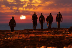 Sechs Wanderer, die bei Sonnenuntergang gehen stockbild