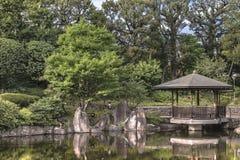 Sechseckiger Gazebo Ukimido im zentralen Teich von Mejiro-Garten wh stockfotografie