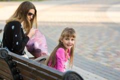 Sechsjähriges Mädchen und Mutter saßen auf Bank für einen Weg, das Mädchen, das froh dem Rahmen betrachtet wurde Lizenzfreie Stockfotos