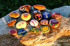 Sechzehn malten Felsen auf einem Flussstein in der Nachmittagssonne Stockfoto