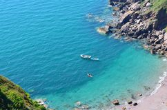 Secluded  Beach with blue sea, boat and canoe Royalty Free Stock Photo