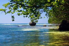 Secluded blue lagoon with  boulder in the sea near Portland, Jamaica royalty free stock photography