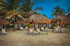 Secluded cabanas on the beach in Cozumel. Deserted cabanas on a beach in Cozumel with a very blue sky and palm trees Stock Photo