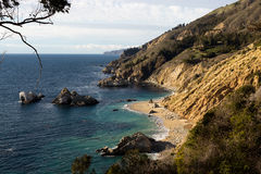 Secluded Californian Beach with White Sand and Turquoise Water. A pristine white sand beach in Big Sur California is met by calm turquoise waters. Rugged Stock Photography