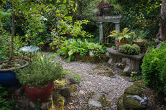 Secluded Garden. An intimate shaded backyard retreat filled with plants, pots, and stone accessories Royalty Free Stock Photo