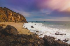 Secluded Pirate's Cove Beach at Sunset. With a colorful sky and ocean water flowing around rock formations, Point Dume, Malibu, California Stock Photo